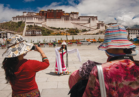 Strike a pose: Han Chinese tourists have overrun Tibet, taking pictures inside temples, gawking at sacred rituals, and making a mockery of a culture.