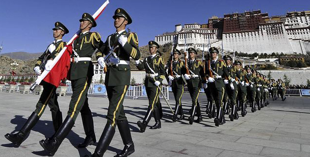 Chinese paramilitary police march during a flag raising ceremony near Potala Palace in Lhasa in northwestern China's Tibet province. AP Photo.