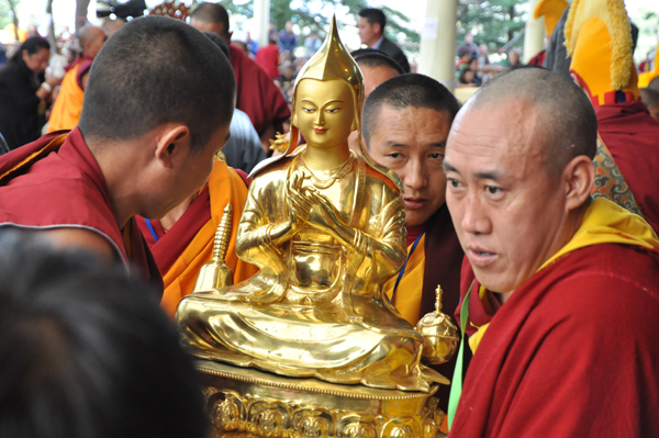 Tibetan monks carry an offering during the long life prayer ceremony