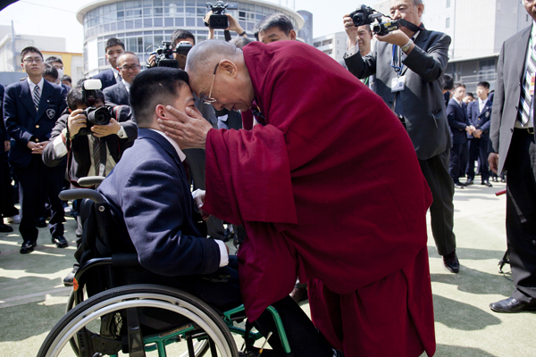 His Holiness the Dalai Lama meets with a physically challenged boy during a talk at Seifu Gakuen Boys High School in Osaka, Japan, on 9 April 2014/Photo/Office of Tibet