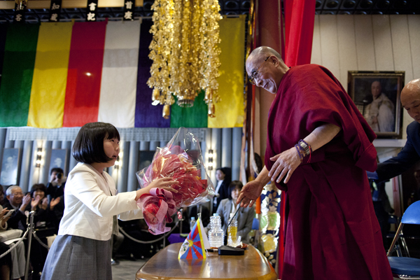 A little Japanese girl presents flowers to His Holiness the Dalai Lama during a public talk at Rinanji Temple in Osaka, Japan, on 9 April 2014/Photo/Office of Tibet