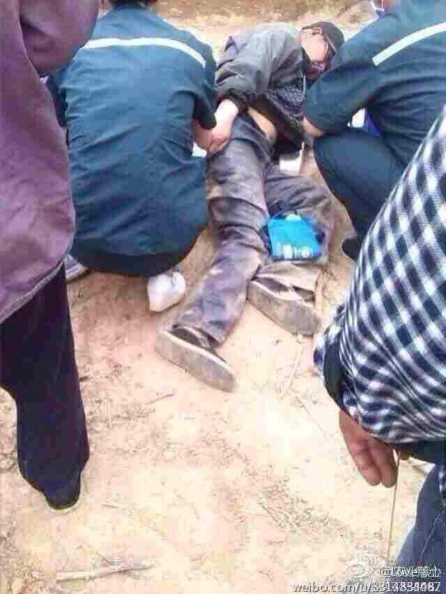 An injured Tibetan protester lying on the ground after the police beatings.