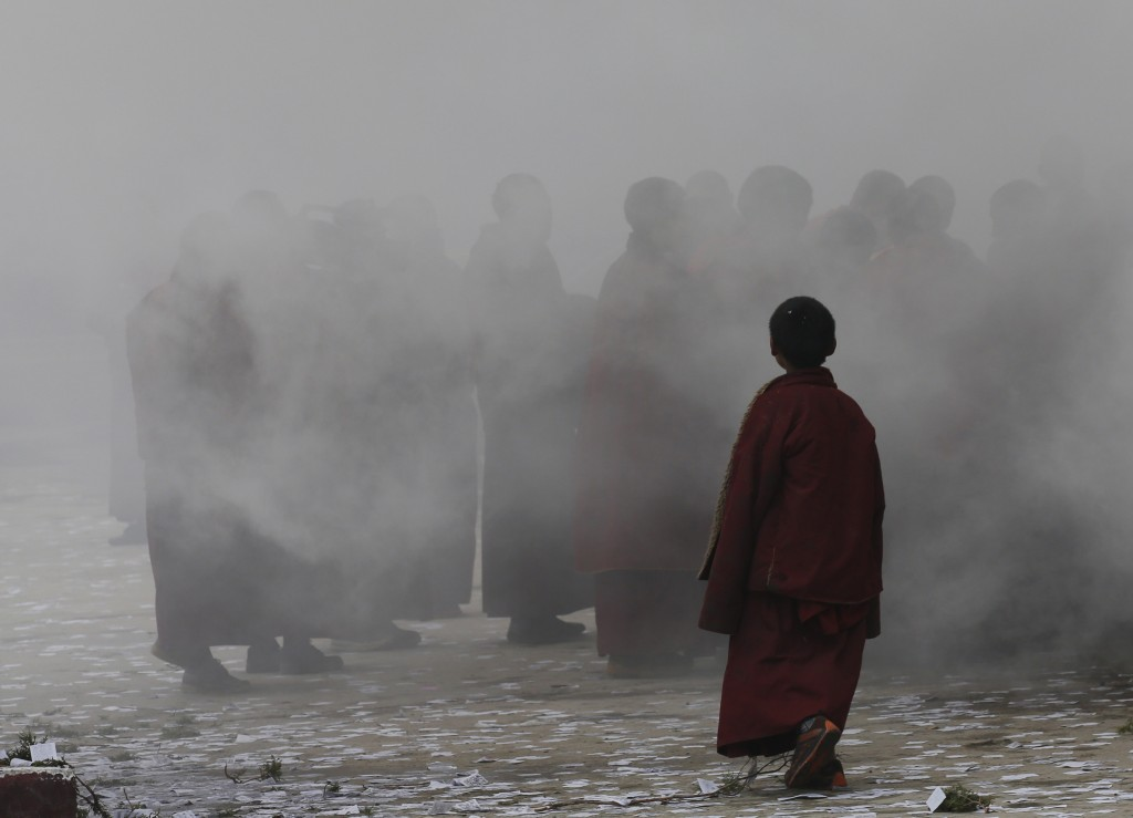 A young Tibetan monk is seen in the smoke as monks burn trees during their morning ritual in the Dzamthang Jonang monastery, where Kalkyi set herself on fire in protest against Chinese rule, in Barma township May 16, 2013. REUTERS/Kim Kyung-Hoon