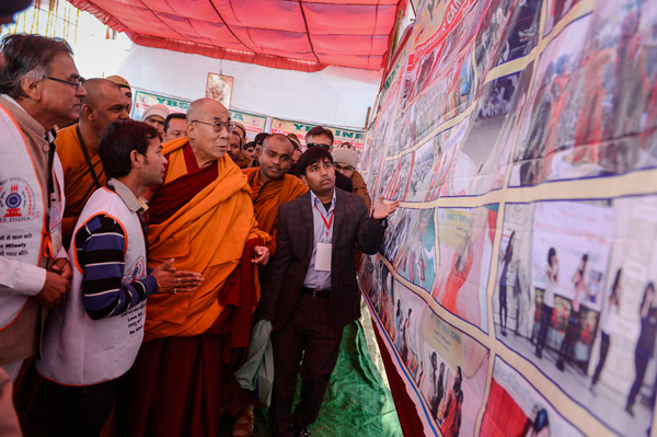 His Holiness the Dalai Lama looking at an exhibit of the activities of the Youth Buddhist Society (YBS) on his arrival at the teaching ground in Sankisa, UP, India on January 31, 2015. Photo/Tenzin Choejor/OHHDL
