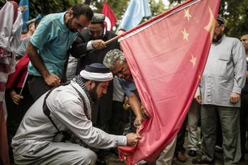 UIghur protestors burn a Chinese flag in Istanbul, where some members of the mostly Muslim ethnic group have settled after fleeing their homeland in China/Associated Press photo