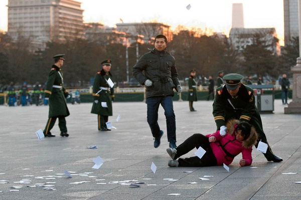 A protester is pushed to the ground by a paramilitary policeman in Beijing on Wednesday before the opening of the National People's Congress nearby. PHOTO: ASSOCIATED PRESS