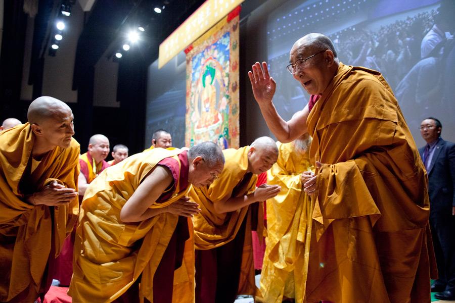 His Holiness the Dalai Lama waving to the audience as he arrives on stage at Showa University Hall at the start of the first day of his two day teaching in Tokyo, Japan on April 12, 2015. Photo/Tenzin Jigmey