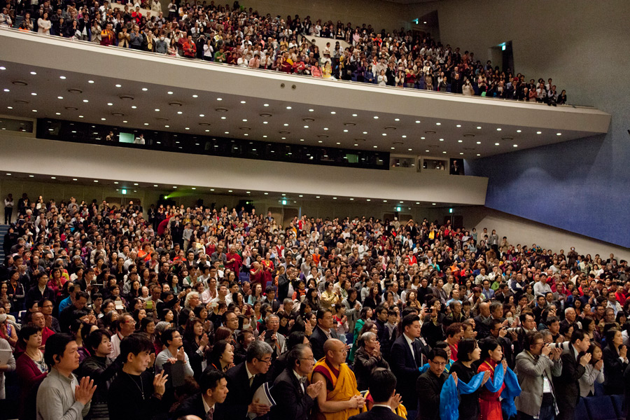A full house of over 2000 people standing as His Holiness the Dalai Lama arrives at Showa University Hall at the start of his teaching in Tokyo, Japan on April 12, 2015. Photo/Tenzin Jigmey