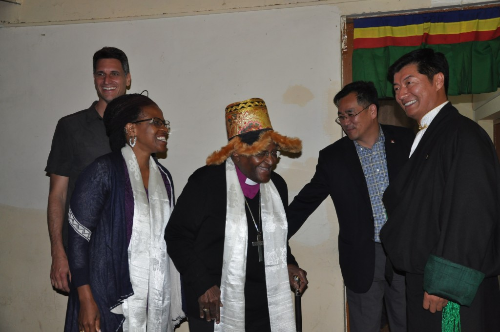A grinning Desmond Tutu reacts with excitement after being put-on a traditional Tibetan hat at the dinner reception, 22 April 2015.
