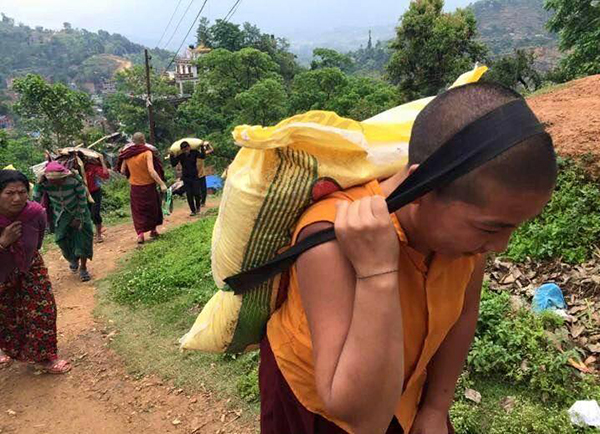 A nun carrying a sack of rice for distribution in a remote village.