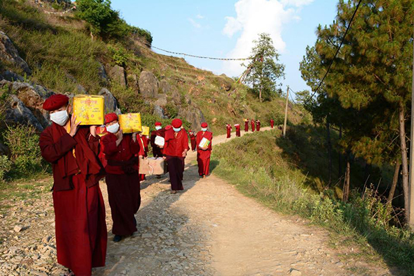 Tibetan nuns carrying boxes of food stuffs for distribution at affected regions.