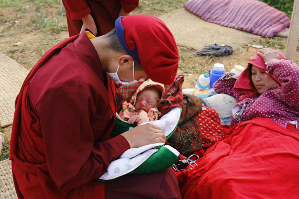 A tibetan nun nursing a new-born baby while the mother rests at temporary shelter in northern Nepal.