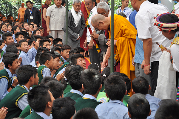 His Holiness the Dalai Lama interacts with a student while departing the teaching venue.