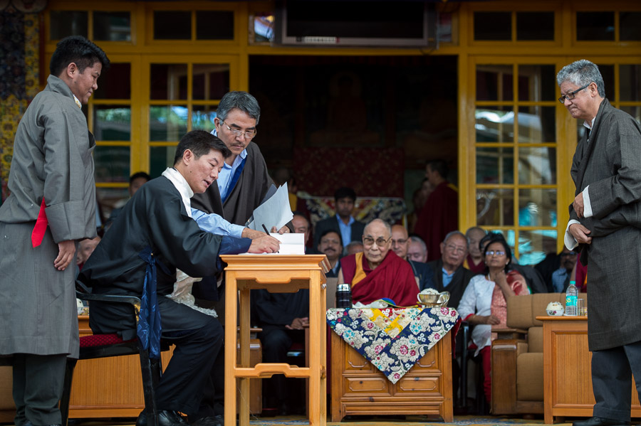 His Holiness the Dalai Lama looks on as Sikyong Dr Lobsang Sangay signs the official book as part of the Sikyong Swearing-in Ceremony held at the Main Tibetan Temple courtyard in Dharamsala, HP, India on May 27, 2016. Photo/Tenzin Choejor