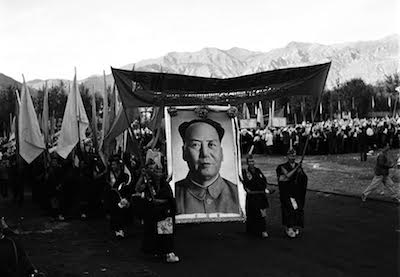"""Two monks with a banner lead a group of monks with a giant portrait of Mao Zedong and flags to celebrate the foundation of the so-called """"Tibet Autonomous Region"""" on September 9, 1965. Less than a year later, the monks and nuns became the target of the wrath of violent Red Guards during the Cultural Revolution."""