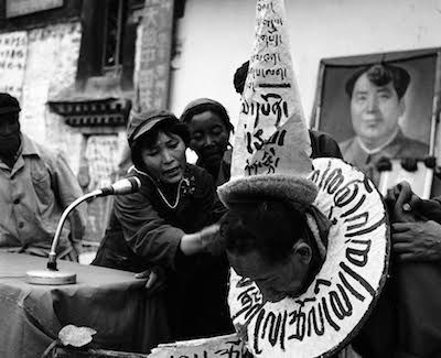 "Tsadi Tseten Dorjee is subjected to a fierce ""struggle session"" by Lugug Achak, the lady wearing a military cap, inside the Jokhang Temple courtyard. Lugug Achak, prior to 1959, was a beggar, commonly known by the name, Lugug Tangpo (beggar). The long placard on Tsadi Tseten Dorjee's chest reads: ""Murderer of the proletariat, key conspirator of the uprising and counter-revolutionary fugitive."""