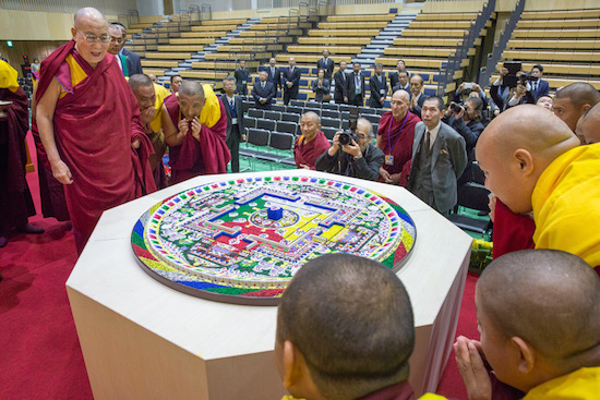 His Holiness the Dalai Lama looking over a sand mandala constructed as part of the inauguration of the new auditorium at Seifu High School in Osaka, Japan on November 10, 2016. Photo/Jigme Choephel