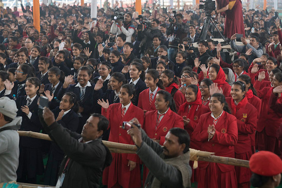 Students in the audience welcoming His Holiness the Dalai Lama as he arrives on stage at the Kalachakra teaching ground in Bodhgaya, Bihar, India on December 31, 2016. Photo/Tenzin Choejor/OHHDL