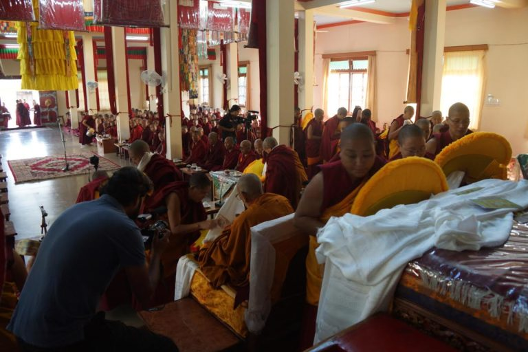 Nuns offering ceremonial Tibetan scarves to portrait of His Holiness the Dalai Lama.