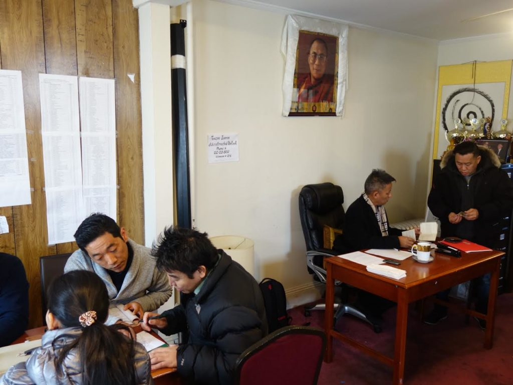 Members of Tibetan community getting in queue to pay Green Book tax.