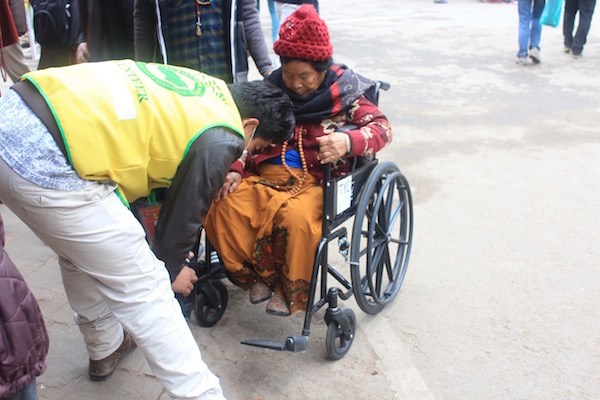 A TYC volunteer helping an aged woman on the wheelchair.