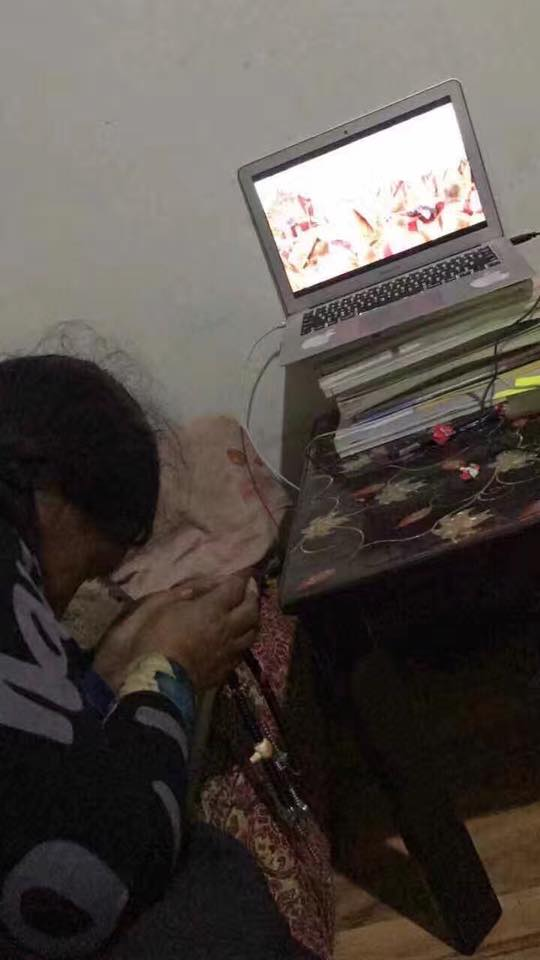 A moving image of an elderly Tibetan woman in Tibet receiving the Kalachakra Teaching online.