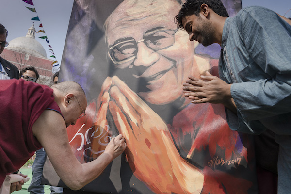 His Holiness the Dalai Lama signing on a live painting created by artist Vilas Nayak at the Itihaas inaugural talk, 6 February 2017.