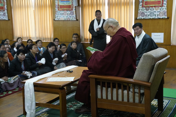 His Holiness the Dalai Lama reading the revised Women Empowerment Policy book