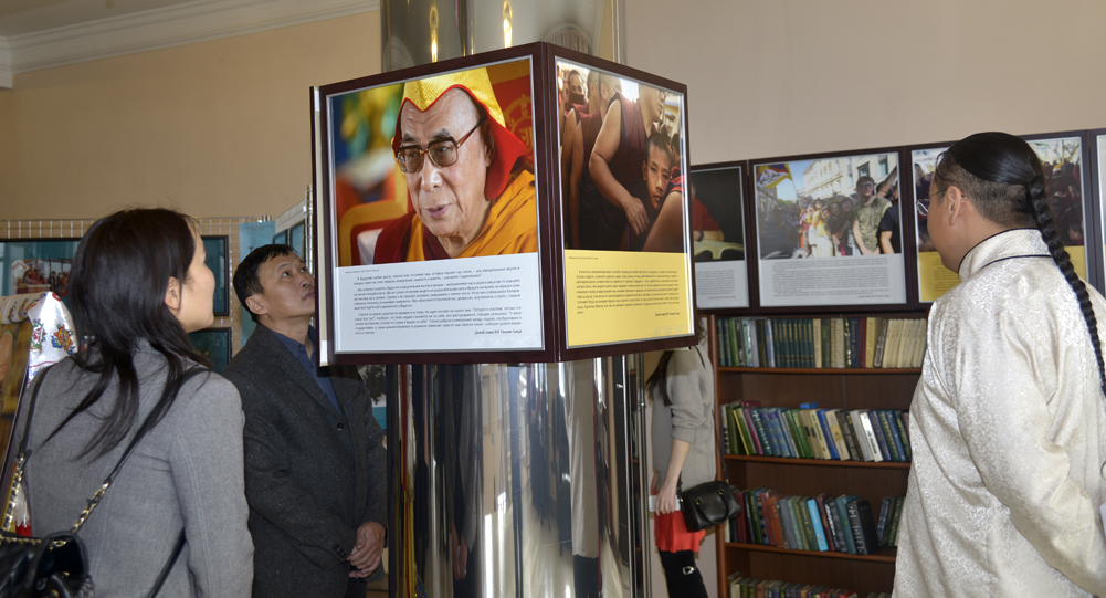 """Local people are going through photos at the exhibition """"The Dalai Lama – As Long As Space Remains"""" in Kyzyl, Tuva, Rusian Federation."""