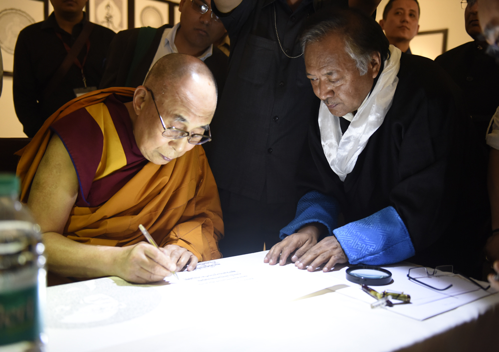 His Holiness the Dalai Lama signing a piece from the exhibition of Tibetan calligraphy by Mr. Jamyang Dorjee at the Rajgir International Convention Centre in Rajgir, Bihar, India on 17 March 2017. Photo/Tenzin Phende/DIIR