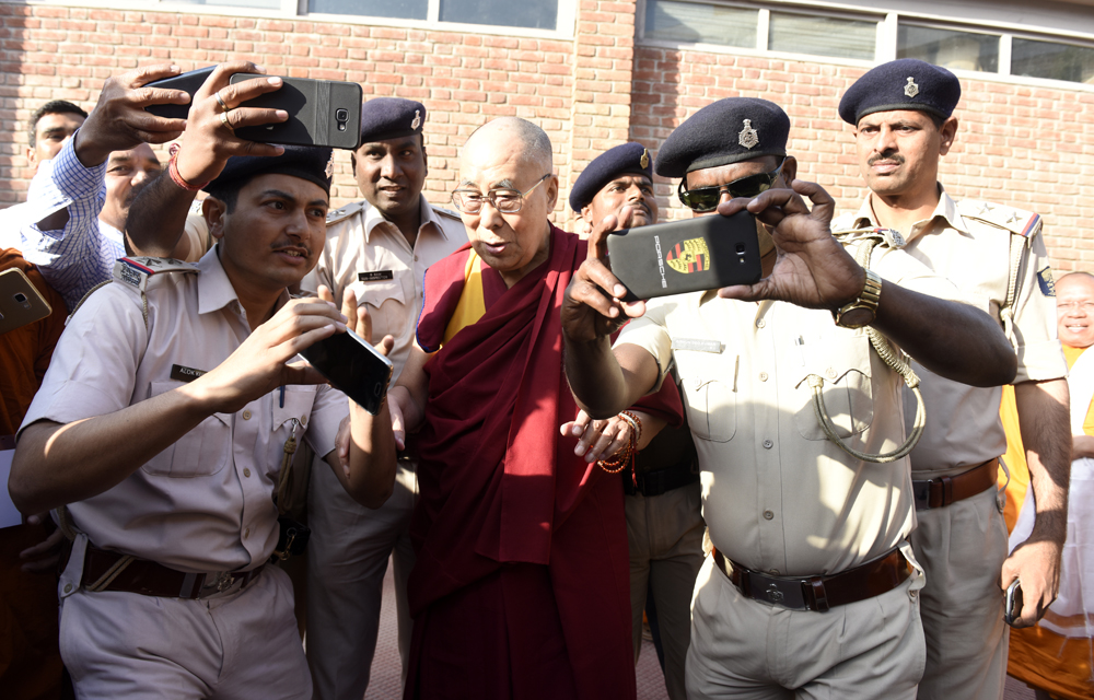 His Holiness the Dalai Lama taking selfies with local police as he leaves his hotel for a visit to Nava Nalanda Mahavihara University in Rajgir, Bihar, India on 18 March 2017. Photo/ Tenzin Phende/DIIR