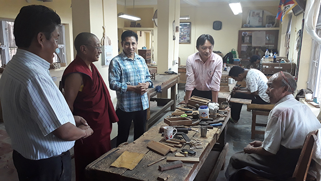 Kalon Karma Gelek Yuthok inspecting the wood carving section of the institute.