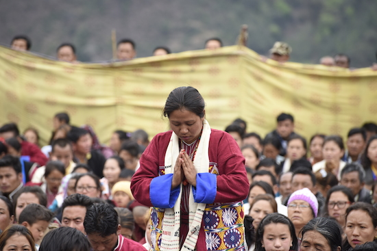 A devotee praying before the teachings by His Holiness the Dalai Lama.
