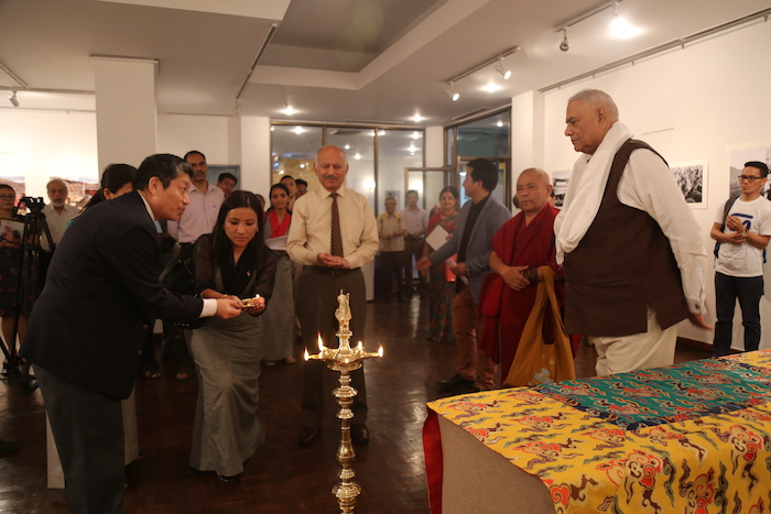 Representative of His Holiness the Dalai Lama in New Delhi, Dhongchung Ngodup Dorjee lights the lamp at the inauguration of the Photo Exhibition on 'Revisiting Cultural Revolution in Tibet.'