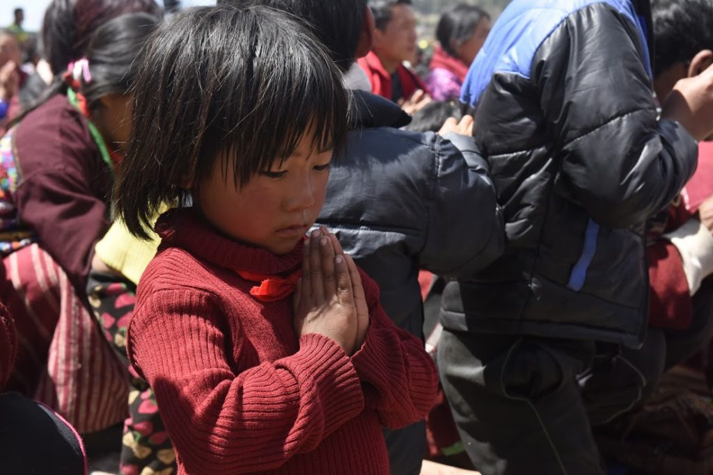 A young girl perform prayers during His Holiness' teachings. Photo @ Jamyang Tsering, DIIR