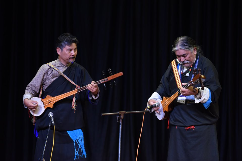 Former Tipa artistes playfully embraces Tibetan instrument (Drumnyal) while performing Tibetan song. Photo|Tenzin Jigme|CTA