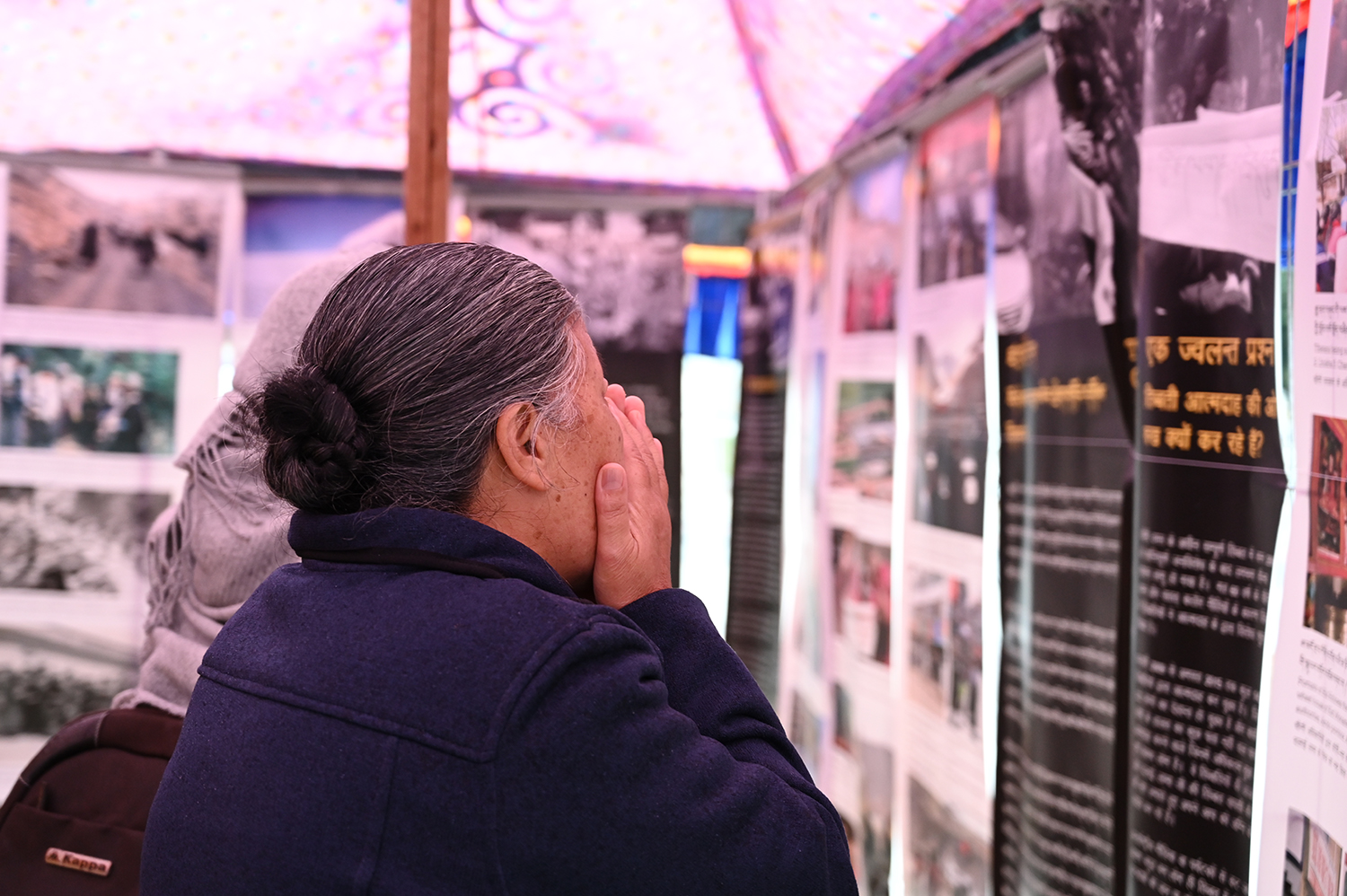 An elderly Tibetan lady going through the exhibition titled: A Long Look Homeward. Photo|Tenzin Nyishon|Switzerland