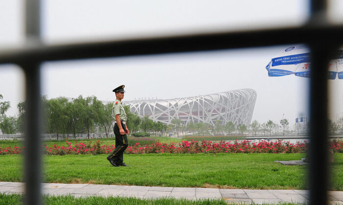 A paramilitary guard patrols the Olympic Green in front of the National Stadium, also known as the Birds Nest, which will host the opening and closing ceremonies as well ast the athletics events during the 8-24 August Beijing Olympic Games on July 2, 2008 in Beijing. (Photo/ FREDERIC J. BROWN/AFP via Getty Images)