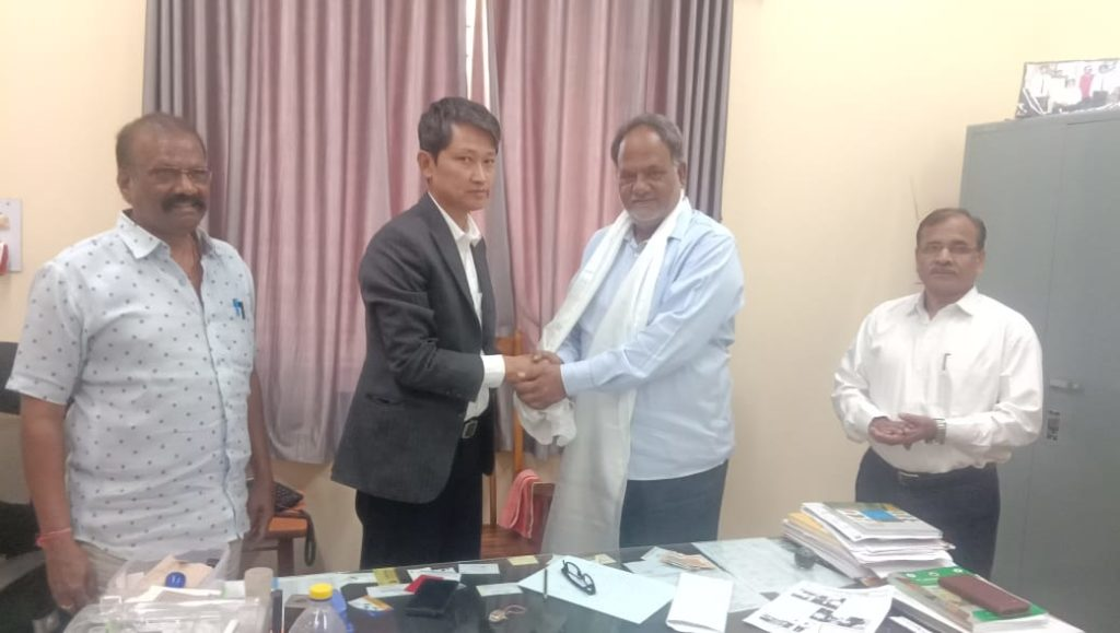 Tibetan settlement officer offers a traditional white scarf to Professor J.S. Hilli at Dharwad Agriculture University.