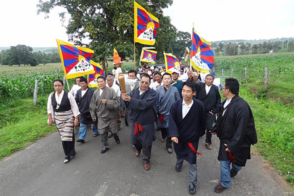 """Exiled Tibetans march with the """"Flame of Truth"""" torch relay in Tibetan settlement of Bylakuppe on 20 July 2012. The torch relay was launched in the Kochi city in Kerala on 6 July 2012."""