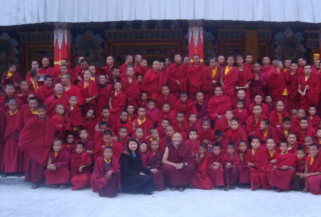 Ngawang Tenzin posing with monks during her health education program in the monasteries, 2013.