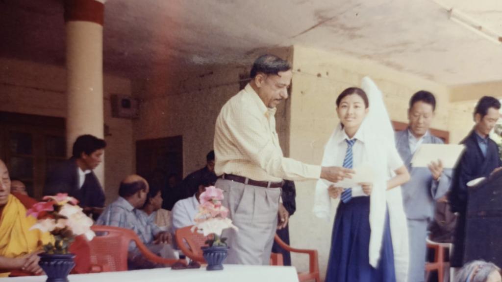 Ngawang Tenzin receiving a school topper achievement award.