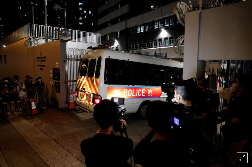 Reporters take pictures and video of a police vehicle driving inside a station where believed members of Hong Kong pro-independence group arrested by the national security unit are held in Hong Kong, China July 29, 2020. REUTERS/Tyrone Siu