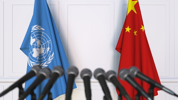 Flags of the United Nations and China at international meeting or negotiations press conference. Photo/VideoHive