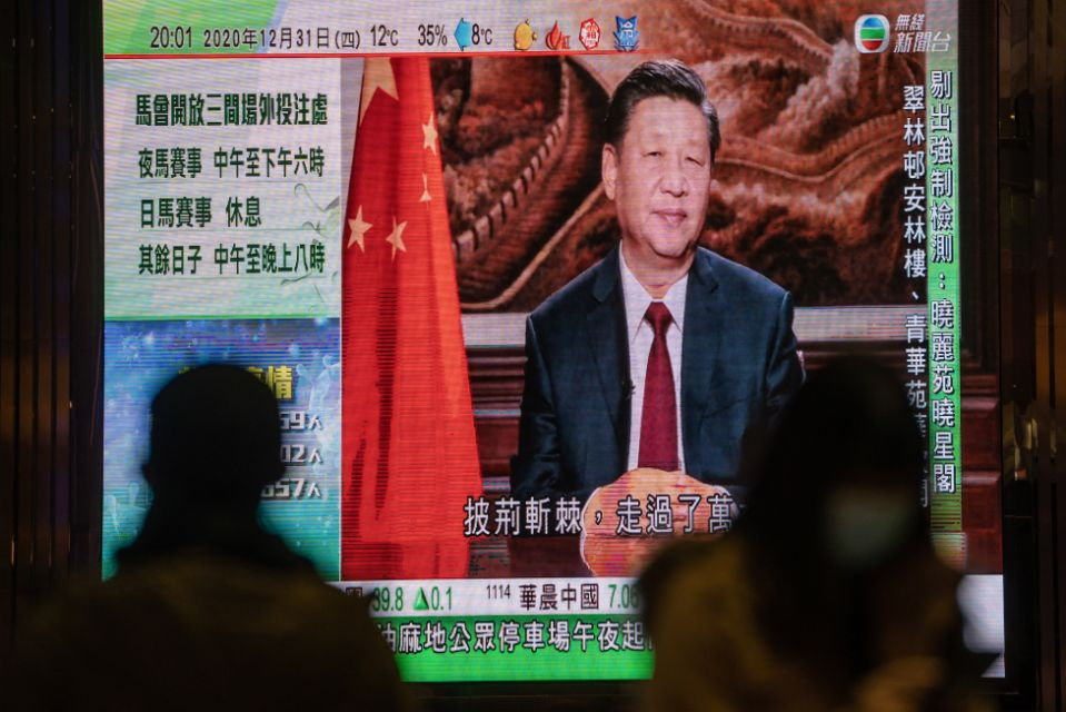 "A news report on Chinese President Xi Jinping's New Year's Eve speech is shown on a public screen in Hong Kong, China, on Thursday, Dec. 31, 2020. This month Xi called on Communist Party officials in the 25-member Politburo to build a ""holistic national security architecture"" that would extend to ""all aspects of the work of the party and the country."" Photographer: Roy Liu/Bloomberg via Getty Images"
